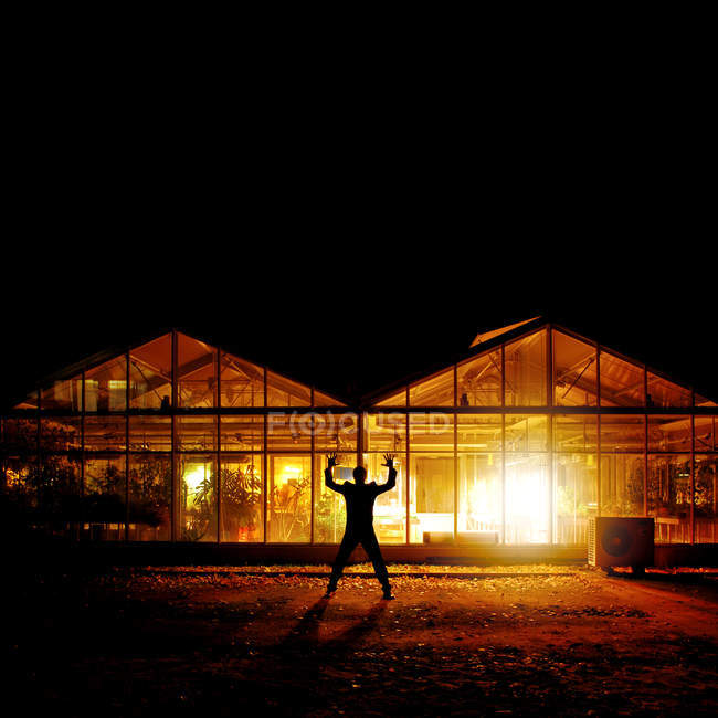 Rear view silhouette of a man standing against an illuminated greenhouse at night — Stock Photo