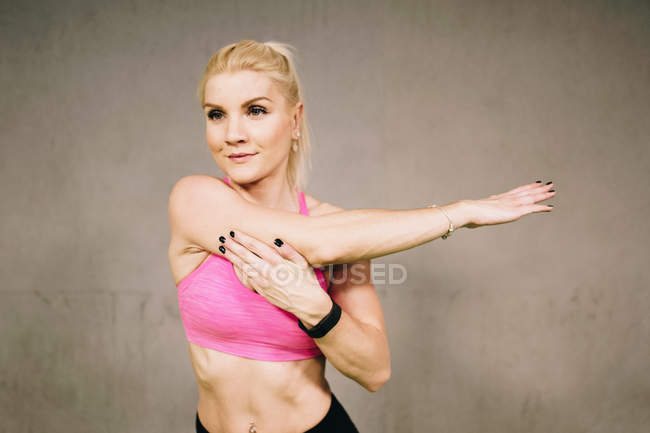 Portrait of young woman standing against gray background and stretching hands — Stock Photo