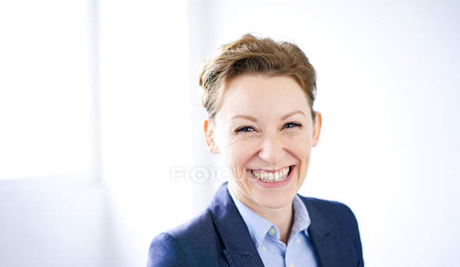 Portrait of smiling business woman in blue jacket and looking at camera — Stock Photo