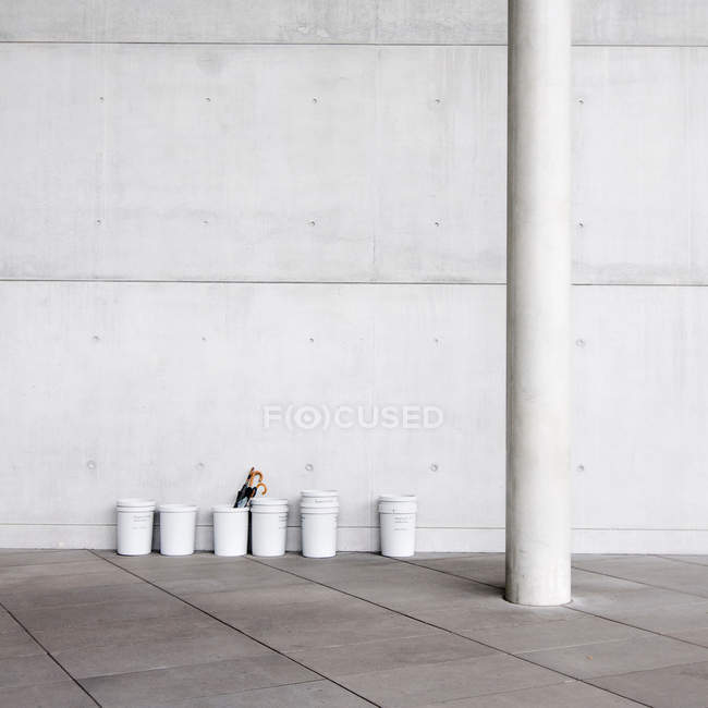 White containers on floor against wall — Stock Photo