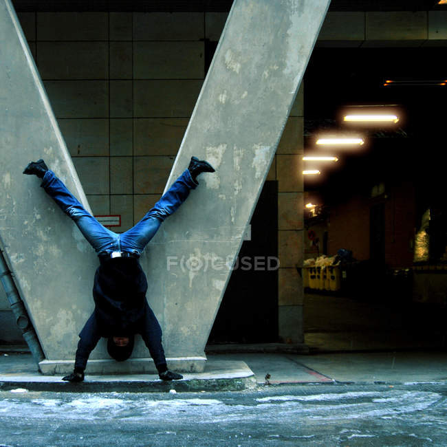 A man doing a handstand against a built structure — Stock Photo
