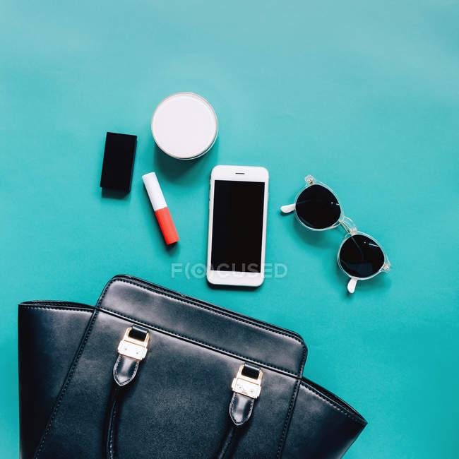 Piatto porre del sacchetto femminile si aprono con cosmetici, occhiali e smartphone su sfondo blu — Foto stock