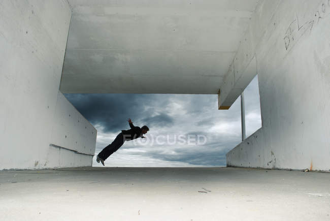 Action shot of a man jumping off a wall — Stock Photo