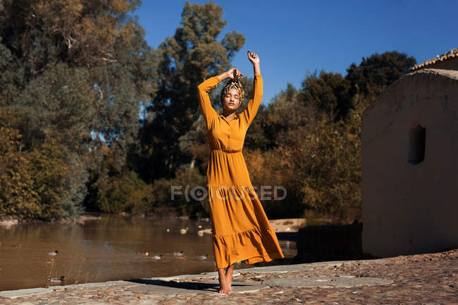 Full length shot of young African woman posing in nature and wearing long yellow dress — Stock Photo
