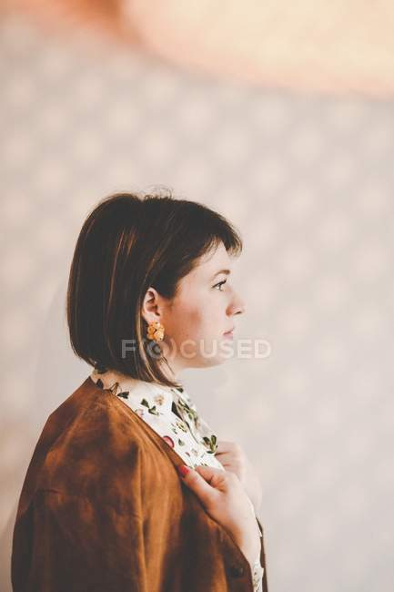 Brunette woman looking away and holding jacket on shoulders — Stock Photo
