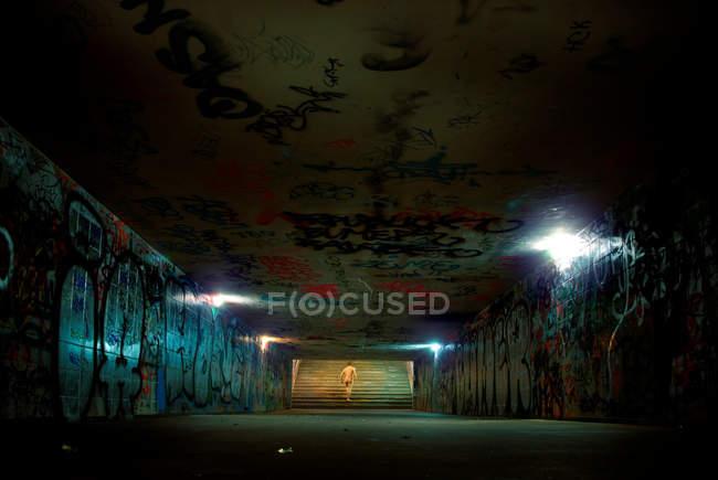 Nackter Mann läuft am Ende eines Tunnels mit graffiti — Stockfoto
