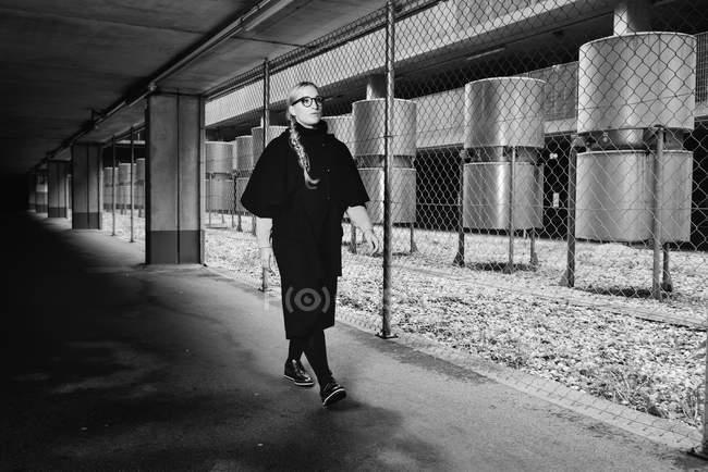 Giovane donna che cammina in ambiente urbano, monocromatico — Foto stock