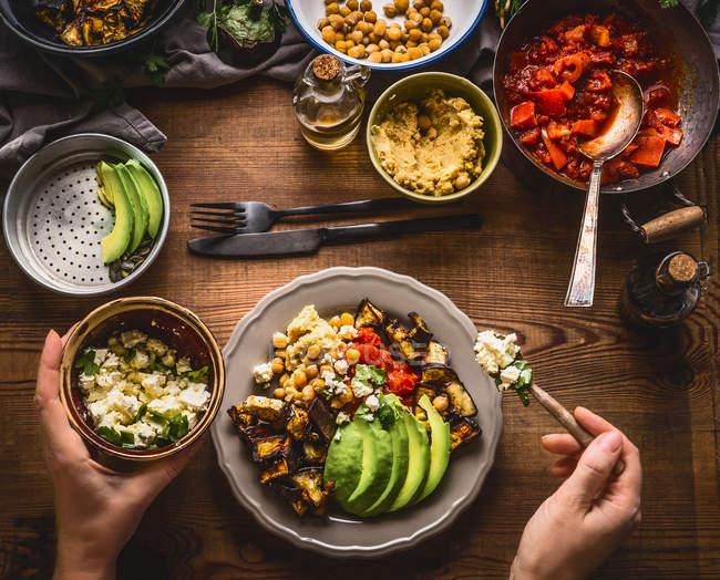 Recortar imagen de comida vegetariana saludable manos humanas es servido - foto de stock