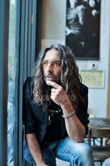 Portrait of a mature long haired man looking out of a window — Stock Photo