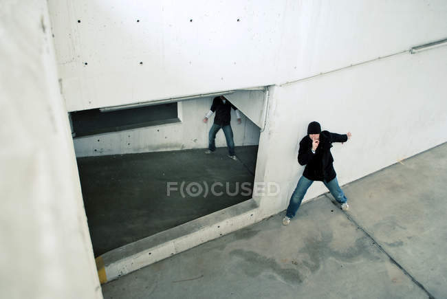 A man hiding from another man in a deserted building — Stock Photo