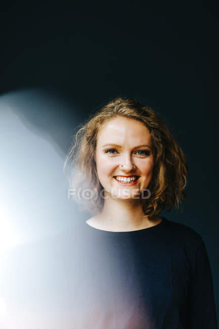 Portrait of positive young woman against black background — Stock Photo