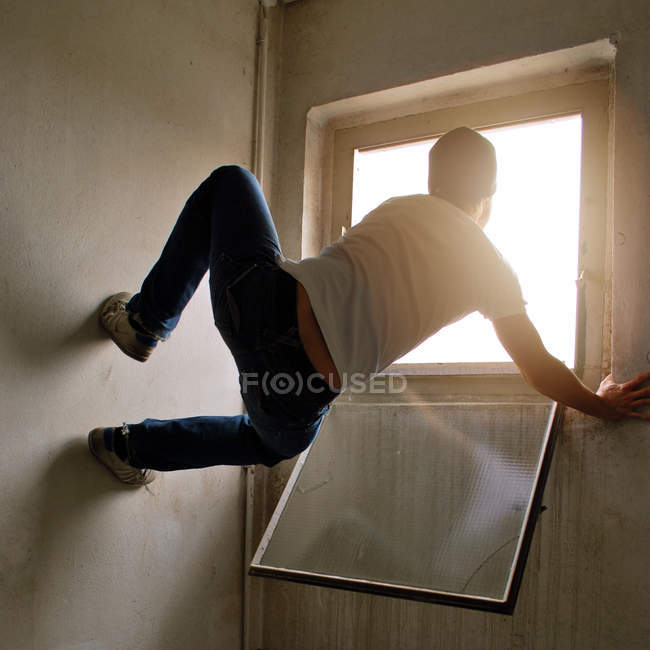 Rear view of a man balancing on a wall looking out of the window — Stock Photo