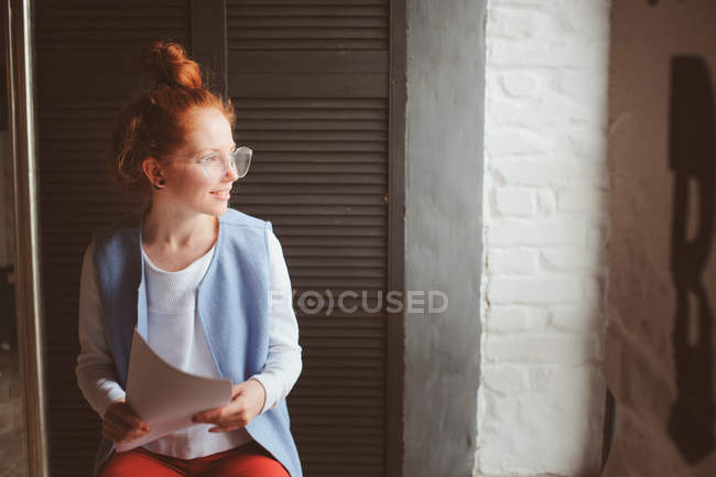A young woman sitting down looking out of a window — Fotografia de Stock
