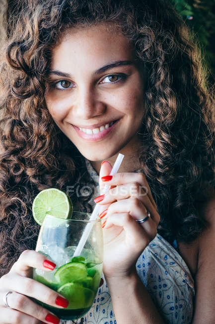 Close-up portrait of a smiling young woman with drink — Stock Photo