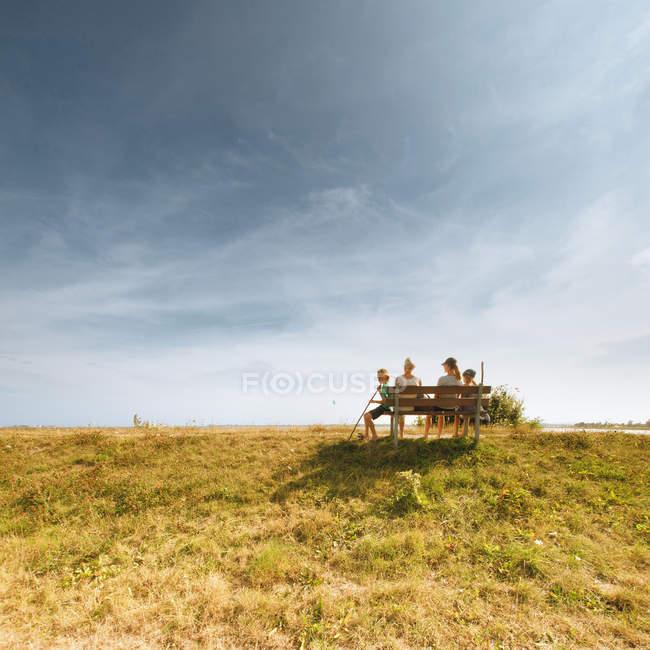 Persone sedute su una panchina in una giornata nuvolosa — Foto stock