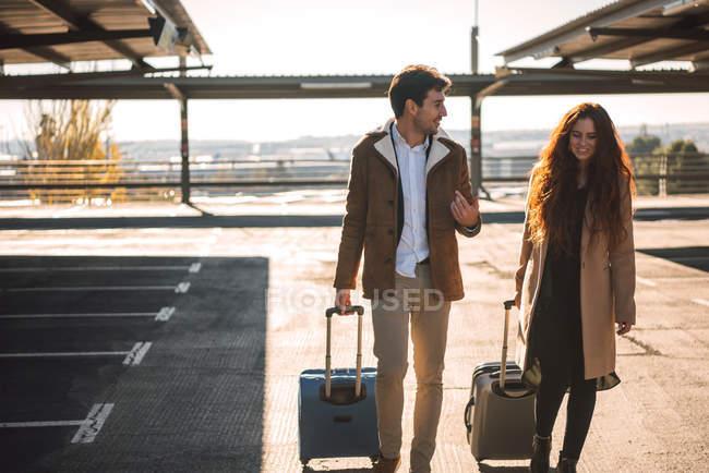b237888c4 Longitud total de pareja en la terminal del aeropuerto caminando con maletas  y sonriendo — Caucásica, marrón - Stock Photo | #202481430