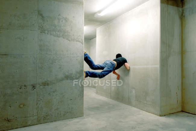 Rear view of a man balancing between two walls — Stock Photo