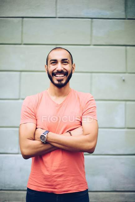 Handsome Hispanic smiling bearded man in casual clothing posing with crossed hands — Stock Photo