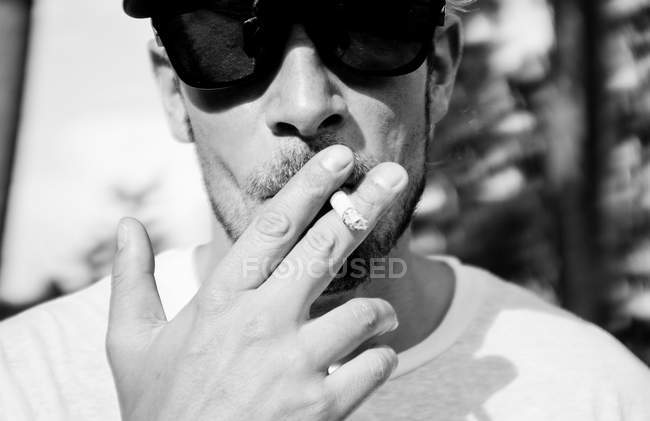 Close-up of cool man in sunglasses smoking cigarette — Stock Photo