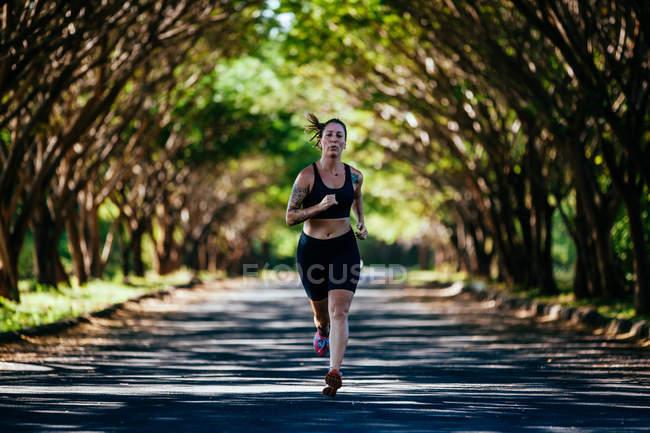 Junge voller Körper Frau läuft auf Tal unter Schatten der Bäume — Stockfoto