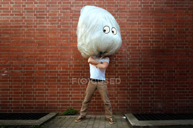Full length of a man standing against a brick wall wearing a funny big white mask — Stock Photo