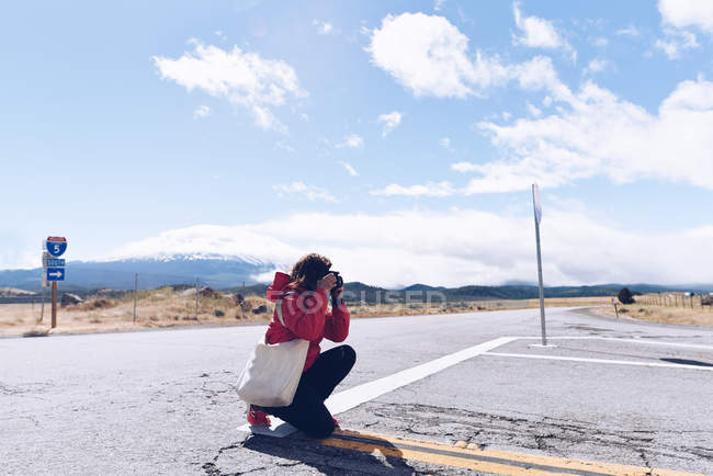 Full length of young woman crouching taking photo — Stock Photo