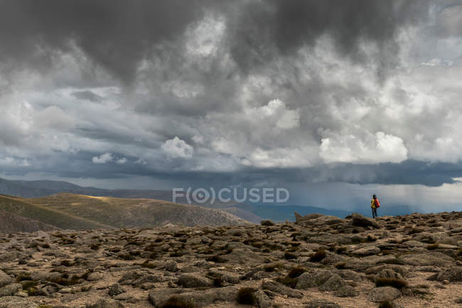 Backpacker standing on hill and looking at dramatic sky above mountains — Stock Photo