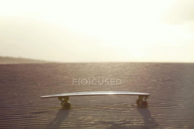 Close-up of skateboard on ground, sunshine on horizon — Stock Photo