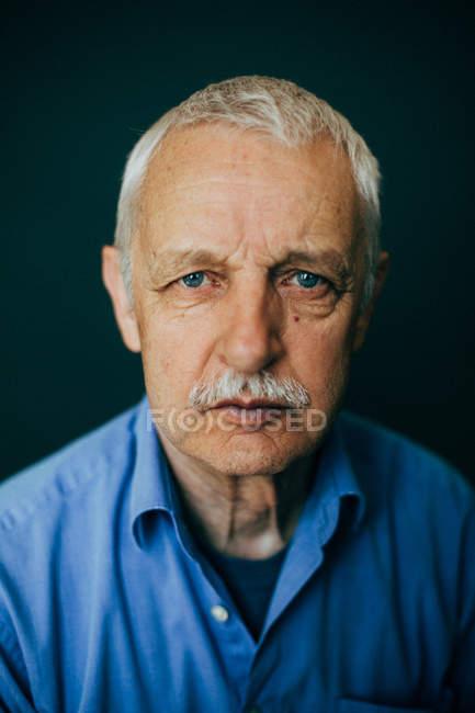 Portrait of mature man against dark background — стокове фото