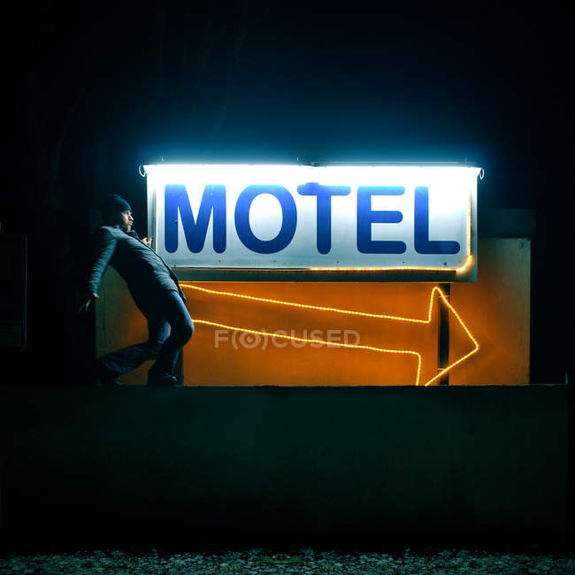 Man walking on a small wall against a neon motel sign — Stock Photo