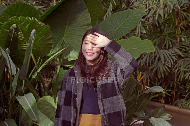 Young asian woman standing at big green palm leaves with closed eyes — Stock Photo