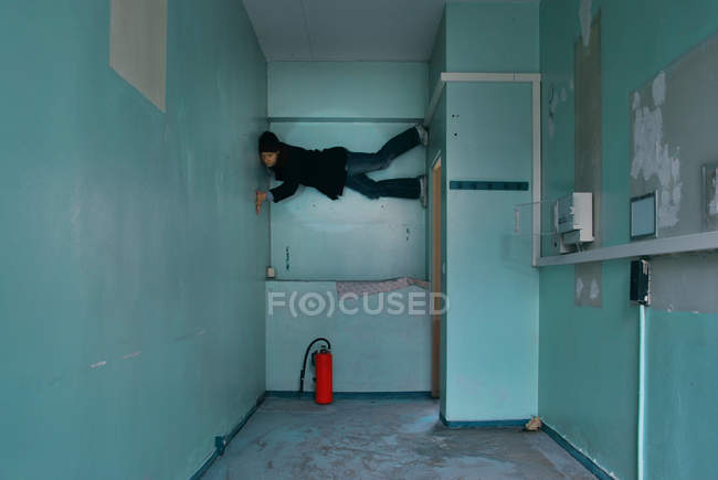 Man balancing between two walls indoors — Stock Photo
