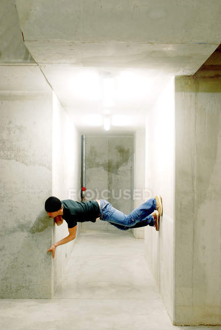 Side view of a man balancing between two walls — Stock Photo