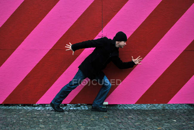 Full length of a young man running against a striped multicolored wall — Stock Photo