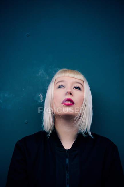 Portrait von blonden Haaren Frau mit Knall Frisur Rauchen und Nachschlagen — Stockfoto