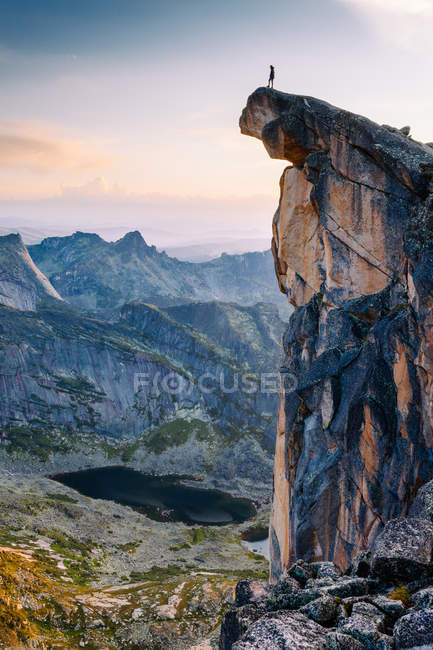 Traveler person standing on rocky mountain peak — Stock Photo