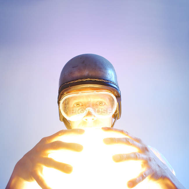 Low angle view of a man in helmet holding an illuminated light — Stock Photo