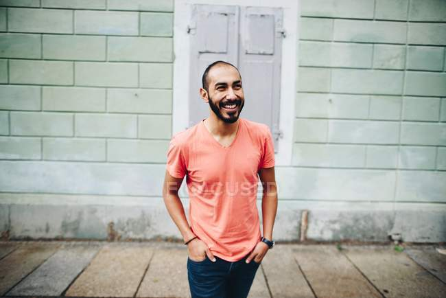 Handsome Hispanic smiling bearded man in casual clothing posing in street at brick building — Stock Photo
