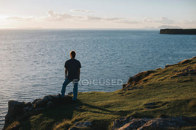 Scenic view of a man looking out at sea — Stock Photo