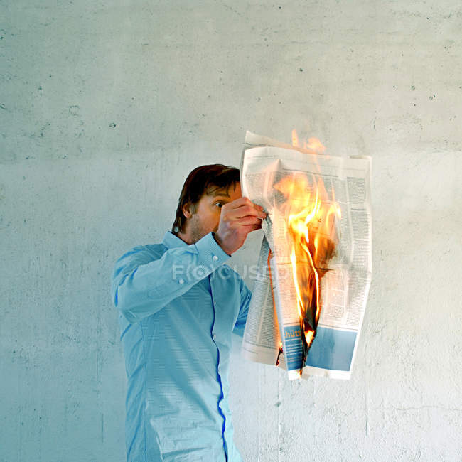 Young man reading a burning newspaper on fire against a white wall — Stock Photo