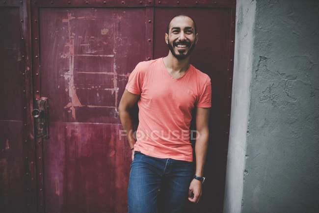 Handsome Hispanic smiling bearded man in casual clothing posing posing at building door — Stock Photo