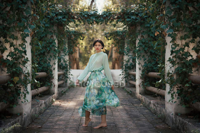 Barefoot woman wearing romantic clothes in pretty garden — Stock Photo