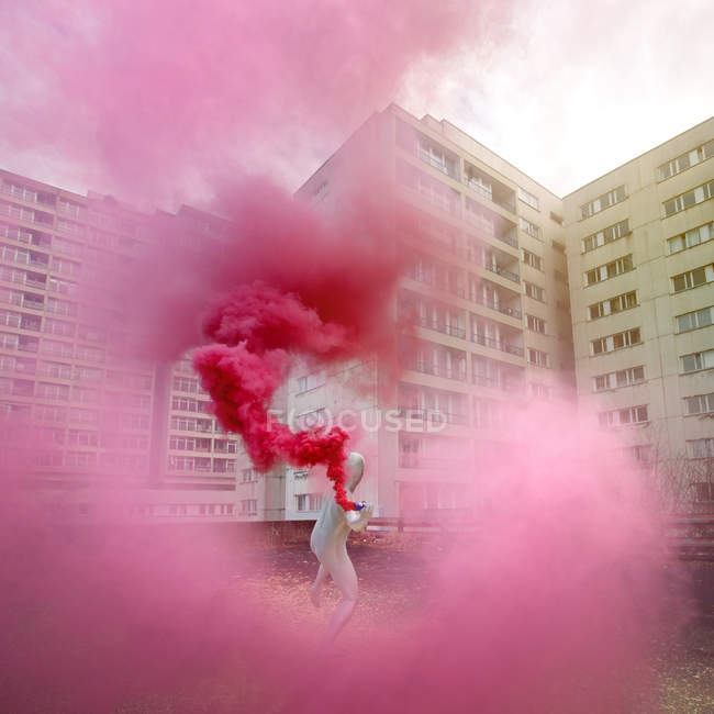 Man in white costume throws pink smoke bomb on roof top of building