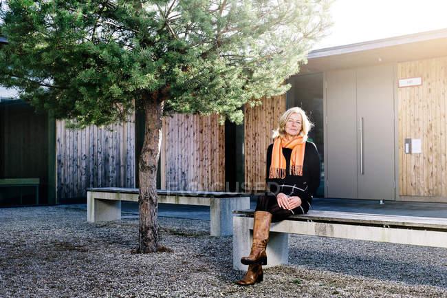 Senior woman sitting on bench at backyard — Stock Photo
