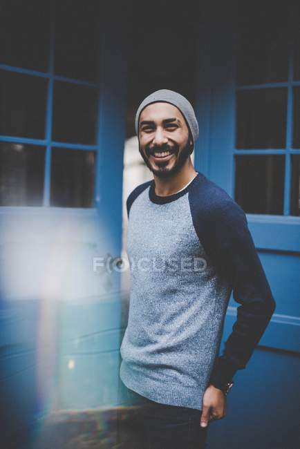 Portrait of smiling young man in hat and casual clothing — Stock Photo