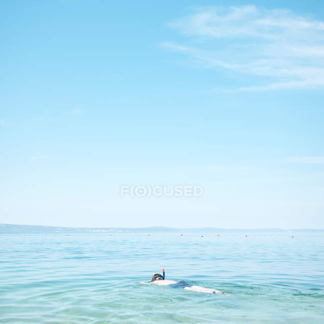 A man swimming in blue sea water with mask — Stock Photo