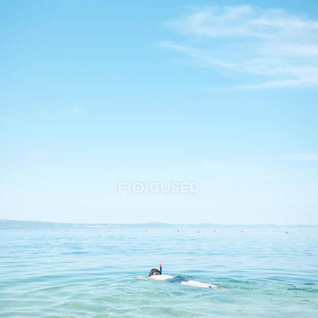 Людина, плавання у воді синє море з маскою — стокове фото
