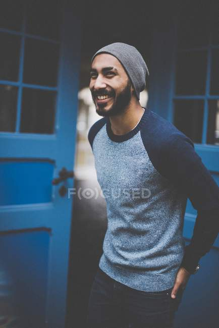 Portrait of happy young man in hat and casual clothing — Stock Photo