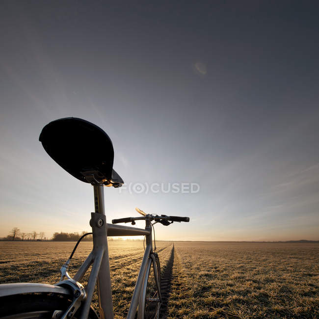 Bicycle overlooking a natural landscape in a field under clear skies in Germany — Stock Photo