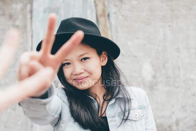 Portrait de femme asiatique à la mode en paix gesticulant chapeau avec les doigts — Photo de stock